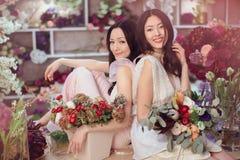 Härliga asiatiska kvinnablomsterhandlare som arbetar i blommalager med mycket vår, blommar Arkivbilder
