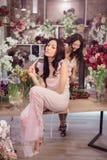 Härliga asiatiska kvinnablomsterhandlare som arbetar i blommalager med mycket vår, blommar Fotografering för Bildbyråer