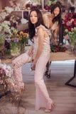 Härliga asiatiska kvinnablomsterhandlare som arbetar i blommalager med mycket vår, blommar Royaltyfri Foto