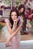 Härliga asiatiska kvinnablomsterhandlare som arbetar i blommalager med mycket vår, blommar Royaltyfria Bilder