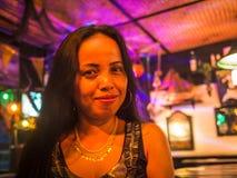 Härliga asiatiska kvinnor ler lyckligt i en bar arkivfoto