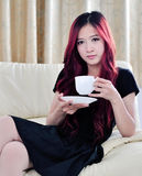 Härliga asiatiska kvinnor med rött långt hår som dricker kaffe Arkivfoto