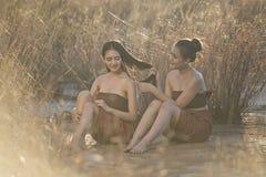 Härliga asiatiska kvinnor som sitter i gräsfältet som bär thailändsk lokal tradition i afton royaltyfri fotografi