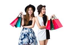 Härliga asiatiska tonåriga flickor som bär shoppingpåsar Royaltyfria Bilder
