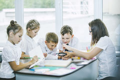 Härliga barn är studenter tillsammans i ett klassrum i schoo Arkivfoto