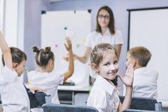 Härliga barn är studenter tillsammans i ett klassrum i schoo arkivbilder