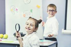 Härliga barn är studenter tillsammans i ett klassrum på set Fotografering för Bildbyråer