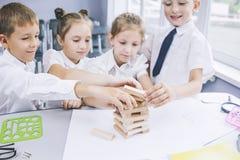 Härliga barn är studenter tillsammans i ett klassrum på set Arkivfoto