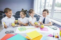 Härliga barn är studenter tillsammans i ett klassrum på set Arkivfoton