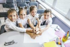 Härliga barn är studenter tillsammans i ett klassrum på set Arkivbilder