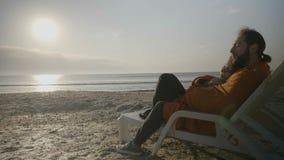 Härliga barnpar som täckas med en filt som kramar och ligger på en vardagsrumstol på stranden som tycker om solnedgången - stock video