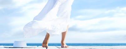 Härliga ben av en ung kvinna i den vita kjolen på en träpir Royaltyfri Foto