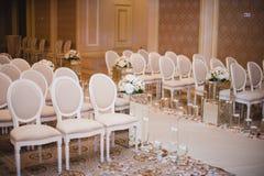 Härliga beståndsdelar för garnering för design för bröllopceremoni med bågen, blom- design, blommor, stolar Royaltyfria Foton