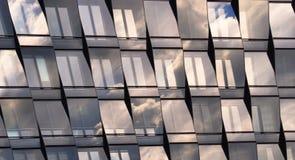 Härliga blåa fönster på en skycraper med moln och himmel arkivfoton