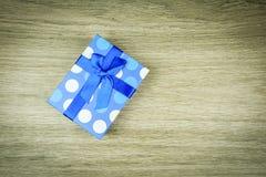 Härliga blått som en gåva med blått pryder med pärlor på en träbakgrund Royaltyfria Bilder