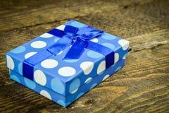 Härliga blått som en gåva med blått pryder med pärlor på en träbakgrund Arkivfoton