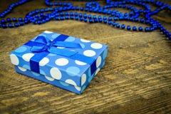 Härliga blått som en gåva med blått pryder med pärlor på en träbakgrund Royaltyfri Bild