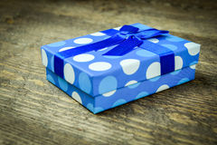 Härliga blått som en gåva med blått pryder med pärlor på en träbakgrund Arkivbild