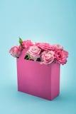 Härliga blommande rosa rosor i dekorativt ordnat för pappers- påse som isoleras på blått arkivfoto