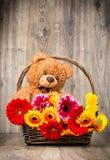 Härliga blommor i korgen och en nallebjörn Royaltyfria Bilder