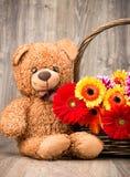 Härliga blommor i korgen och en nallebjörn Royaltyfri Bild