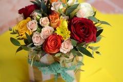 Härliga blommor i vas på en tabell i ett rum Arkivfoton