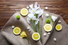 Härliga blommor och citronskivor med säckväv på träbackgro arkivfoto