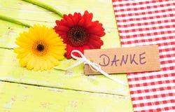 Härliga blommor och kortet med det tyska ordet, Danke, hjälpmedel tackar dig Arkivbilder
