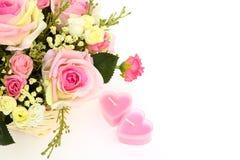 Härliga blommor och två hjärtastearinljus som isoleras på vit med s Royaltyfria Bilder