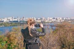 Härliga blonda flickadanandefoto av staden på en smartphone Royaltyfri Foto