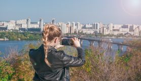Härliga blonda flickadanandefoto av staden på en smartphone Royaltyfri Bild