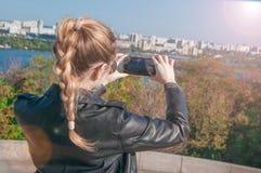 Härliga blonda flickadanandefoto av staden på en smartphone Royaltyfria Bilder