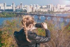 Härliga blonda flickadanandefoto av staden på en smartphone Arkivbilder