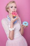 Härliga blonda kvinnor smakar den färgrika efterrätten skjutit mode soft för fält för färgpildjup grund Royaltyfri Fotografi