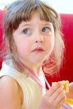 Härliga blonda små förvirrar bekymrat, att kallat och gett reprimand, medan tugga ett stycke av kakan på ett födelsedagparti royaltyfria bilder