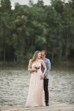 Härliga brölloppar, brud, ansar att kyssa och att posera på bron nära sjön Royaltyfri Fotografi