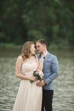 Härliga brölloppar, brud, ansar att kyssa och att posera på bron nära sjön Royaltyfri Foto