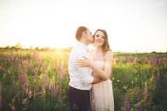 Härliga brölloppar, förälskelse på solnedgången Fielf med blommor Arkivfoto