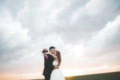 Härliga brölloppar, förälskelse på solnedgången Fielf med blommor Royaltyfri Fotografi