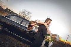 Härliga brölloppar i bygden bredvid den retro bilen manbrudgummen tar den hållande bruden i hans armar le lycklig ch Royaltyfri Fotografi