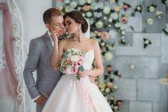 Härliga brölloppar som kramar i ljus studio Brudgummen i en affärsgrå färg passar, en vit skjorta i en fluga och a royaltyfria foton