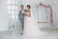 Härliga brölloppar som kramar i ljus studio Brudgummen i en affärsgrå färg passar, en vit skjorta i en fluga och a royaltyfri fotografi