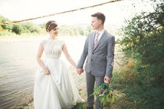 Härliga brölloppar som kysser och omfamnar nära kusten av en bergflod med stenar Royaltyfri Fotografi