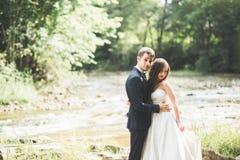 Härliga brölloppar som kysser och omfamnar nära kusten av en bergflod med stenar Fotografering för Bildbyråer