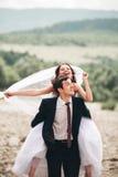 Härliga brölloppar som kysser och omfamnar nära kusten av en bergflod med stenar Arkivbilder