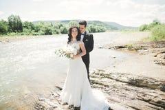 Härliga brölloppar som kysser och omfamnar nära kusten av en bergflod med stenar Royaltyfria Bilder