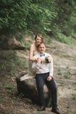 Härliga brölloppar som kysser och omfamnar nära kusten av en bergflod med stenar Arkivfoto