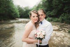 Härliga brölloppar som kysser och omfamnar nära kusten av en bergflod med stenar Royaltyfri Bild