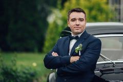 Härliga brölloppar som poserar nära den storartade retro bilen arkivfoto