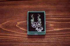 Härliga brudörhängen med stenar i den blåa asken, modetillbehör som gifta sig garneringar på en brun träbakgrund fotografering för bildbyråer